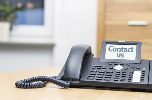 modern voip telephone on wooden desk saying CONTACT US