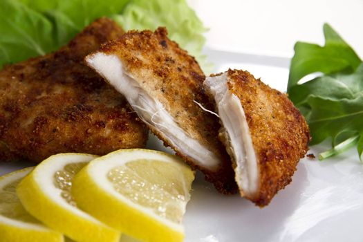 Breaded chicken breast with lemon and salad