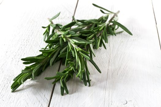 Fresh rosemary on white wooden table