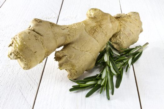 Fresh ginger and rosemary on white wooden table