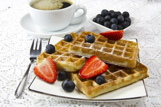 Freshly baked waffles with berries and coffee