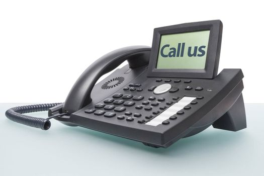 modern business voip phone on glass desk with the words - Call us - in the display