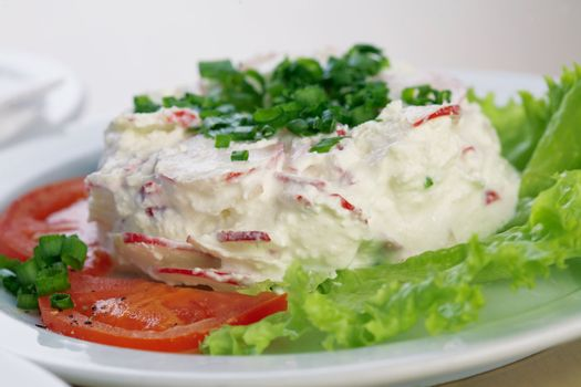 Close-up picture of a radish salad with lettuce, tomato, parsley and mayonnaise on the plate.