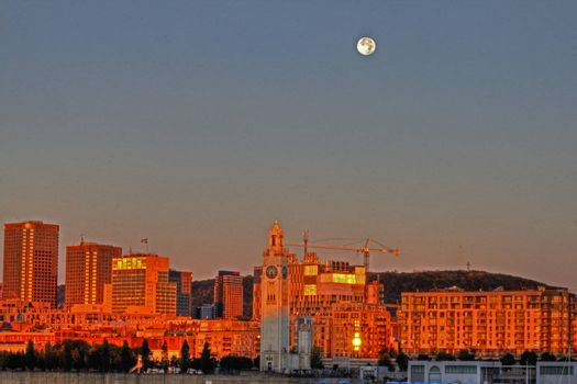 Sunrise with full moon over Montreal cityscape