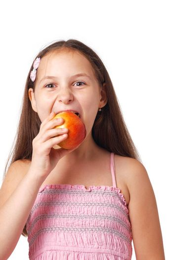 Nice  little girl eating a delicious apple against white.