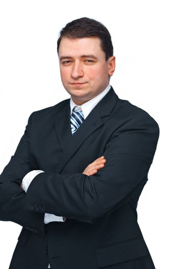 Portrait of a successful business man in a black suit with hands folded isolated over white