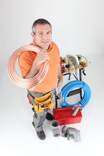 Plumber holding copper piping with various other materials