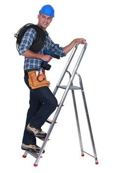 A tradesman climbing a stepladder