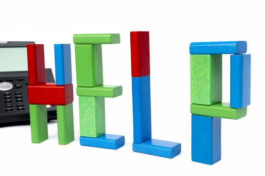 the word help made with toy bricks and a phone in background. isolated on white background