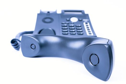 simple blue business phone on white background. telephone receiver in the front