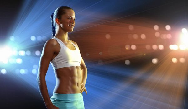 Fitness woman standing against color lights background