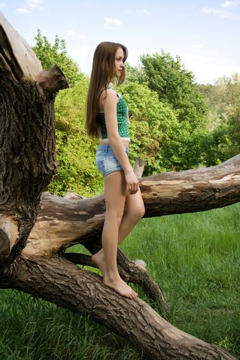Pretty girl leaning against a tree in denim shorts and a t-shirt