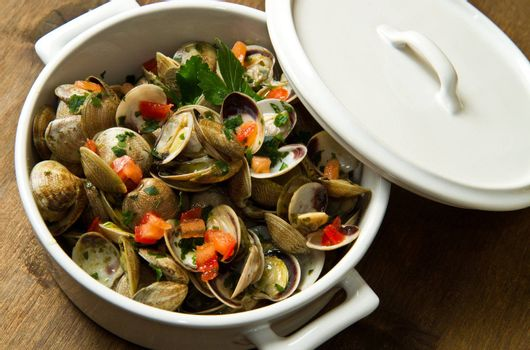 a delicious clams soup with tomatoes on white bowl
