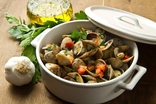 bowl with delicoius clams soup on wooden table
