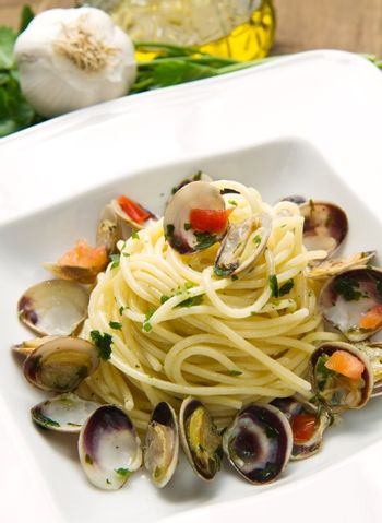 dish of spaghetti with clams on wooden table