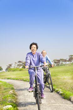 asian seniors couple biking in the park