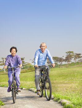 Happy asian seniors couple biking in the park