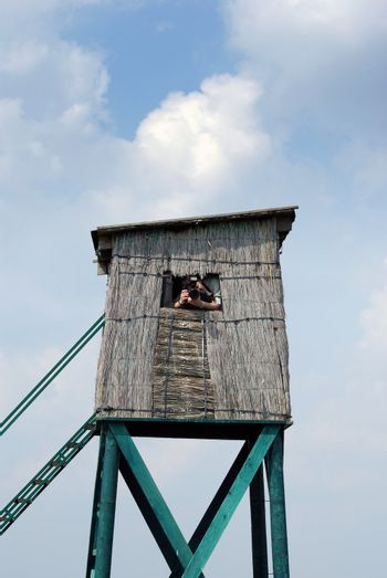 Photographer waiting for wild animals in hunting blind
