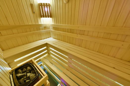 Finnish sauna. Small room with shelves and electric heater stones.