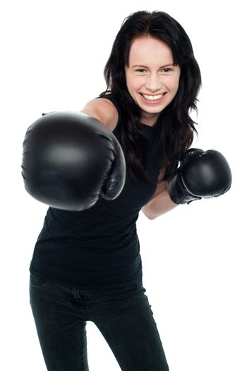 Smiling young female boxer ready to punch you