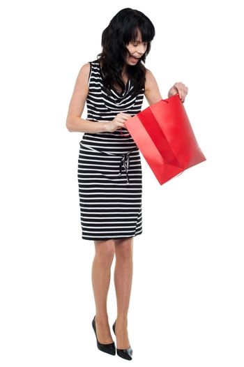 Young woman searching for her gift inside bag