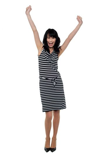 Full length portrait of a jubilant young woman celebrating her success.