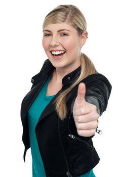 Joyful blonde teen gesturing thumbs up