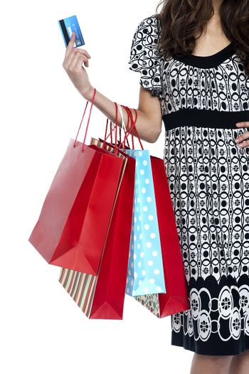 Stylish woman walking with shopping bags and credit card, cropped image on white background.