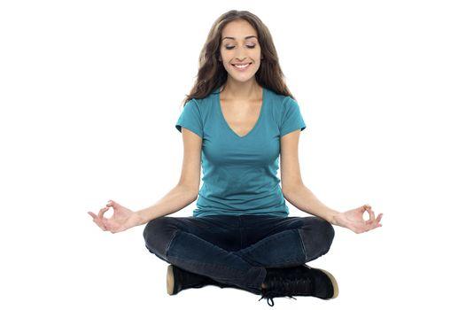 Smiling woman meditating in lotus position