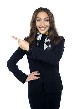 Friendly smiling stewardess pointing away