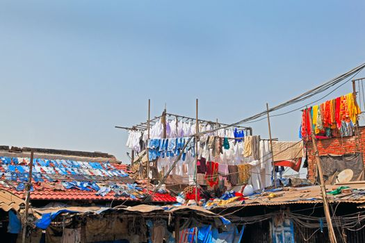 Denim drying on slate roofs and clothes in hand made bamboo racks at commercial laundry in Bombay India