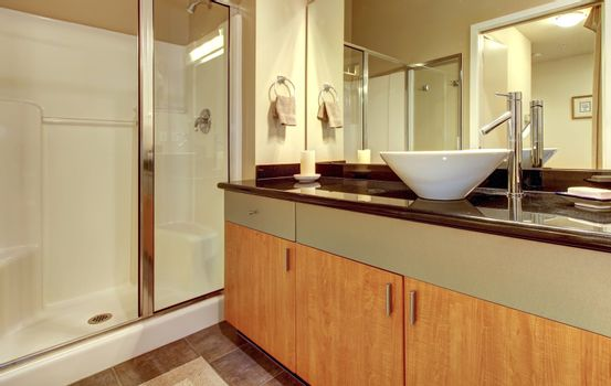 Bathroom with wood modern cabinets and white sink.