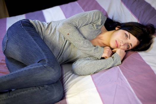 Depressed young woman in bed after domestic violence at home