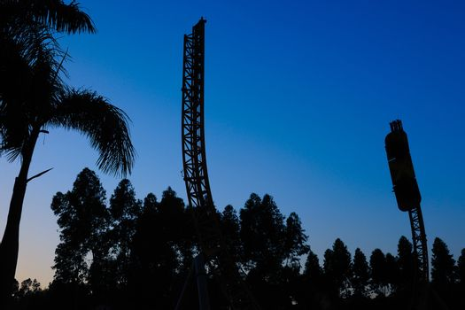 Silhouette of recreational facilities in the amusement park under blue sky