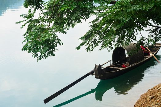Fishing boat on the river under the tree in Hunan province of China
