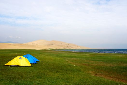 Tent on the lawn near the lake and sand dunes in qinghai province of China