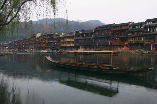 China river landscape with boat and ancient building in Fenghuang county, Hunan province, China