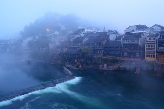 Foggy river landscape with Chinese traditional wooden buildings as background