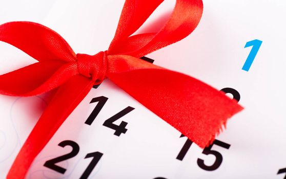 Sheet of wall calendar with red bow on Valentines day