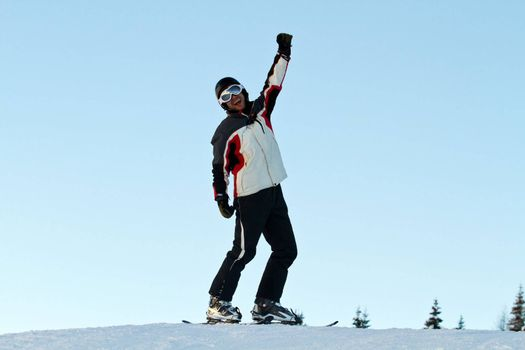 portrait of skiers throwing up her hands on the slopes in a sunny day