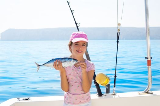 child little girl fishing in boat holding little tunny tuna fish catch with rod and trolling reels
