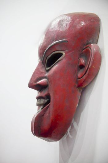 Vertical take of a generic mounted hand carved smiling mask. Shot location India