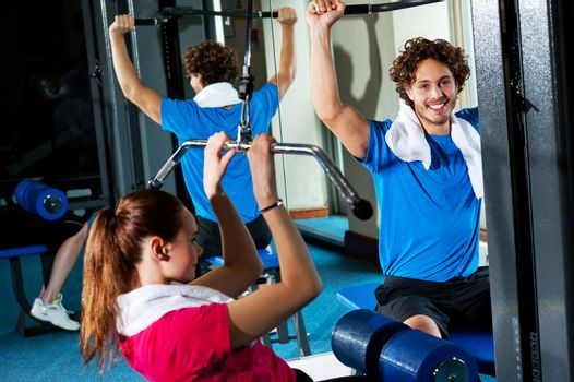 Friends working out together in a multi gym
