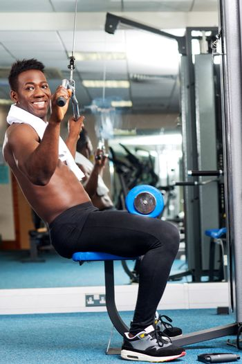 Fit african trainer working out in multi gym