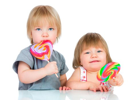 Babies eating a sticky lollipop on white background