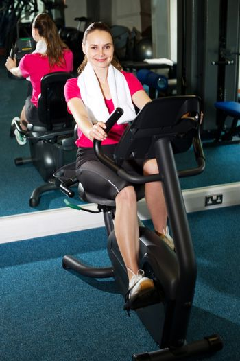 Pretty fit woman pedaling exercise bike fast