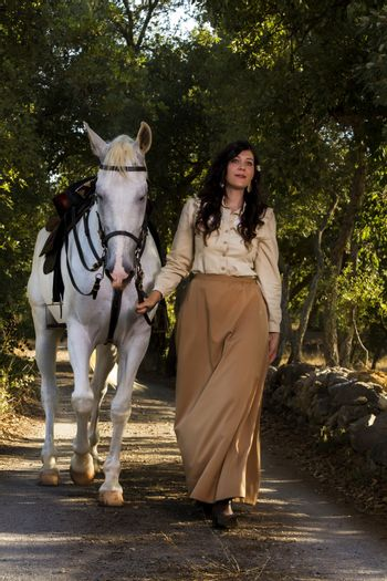 View of a beautiful girl in classic dress with a white horse on the countryside.