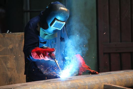 welders with protective mask in the factory