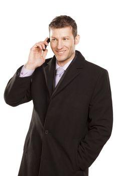 smiling man in a coat telephones