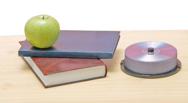 Apple, dvd, and books as a symbol of transition fron old to new mways of learning